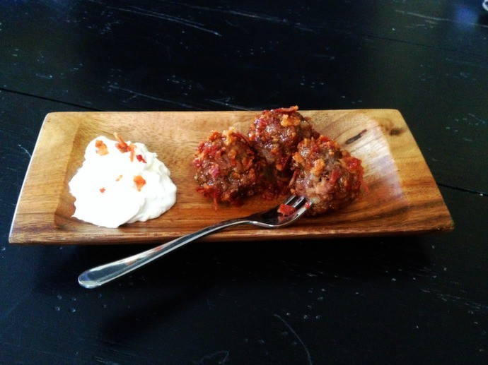 Side view of chipotle meatballs and bacon cream cheese on a wood platter