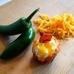 Jalapeno cornbread muffin, shredded cheese and jalapenos on a cutting board
