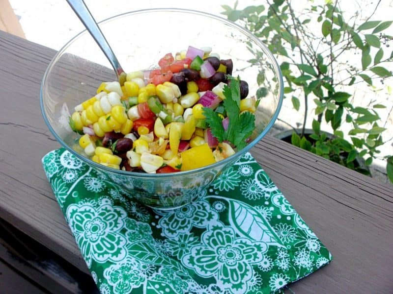 Summer Corn Salad in glass bowl with a serving spoon in it