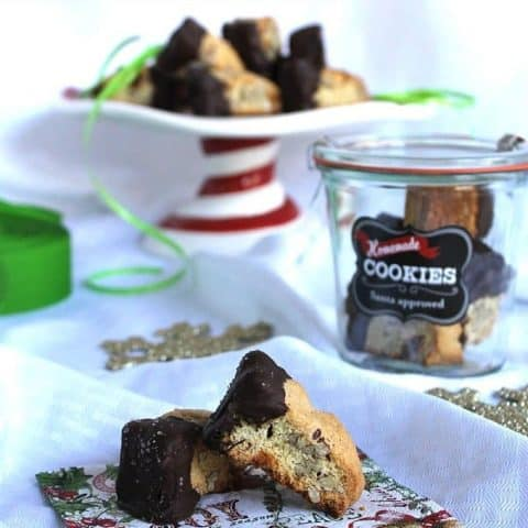 Dark Chocolate Salted Caramel Almond Biscotti on a festive napkin, in a container and on a server platter