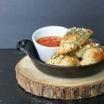 Side view of Garlic Knots and a small white bowl with tomato sauce in a black serving dish