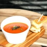 Grilled tomato soup in a white bowl and grilled cheese bites on a cutting board