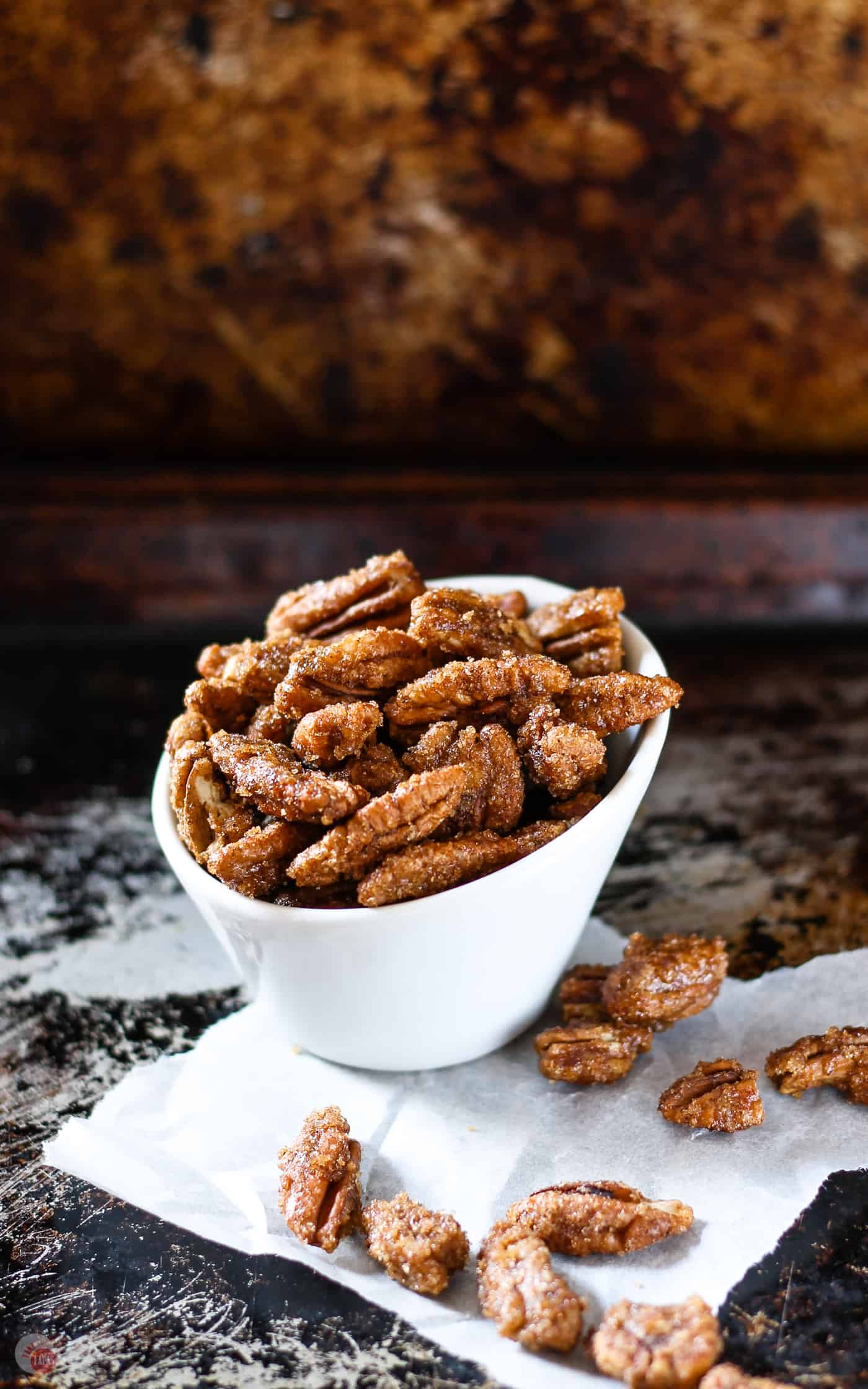 side view of gingersnap pecans in a white bowl