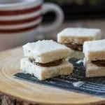 Chocolate caramel shortbread sandwiches on a wood serving platter.