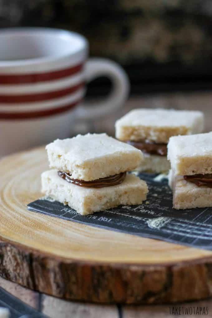 Chocolate caramel shortbread sandwiches on a wood serving platter.