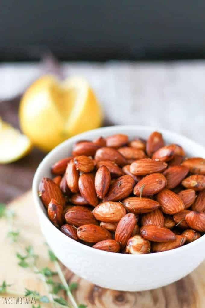 Close up of almonds with lemon thyme in a bowl