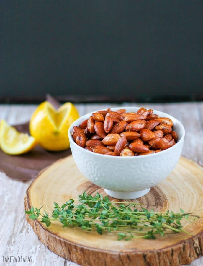 Toasted Lemon Thyme almonds in a white bowl sitting on a wood platter