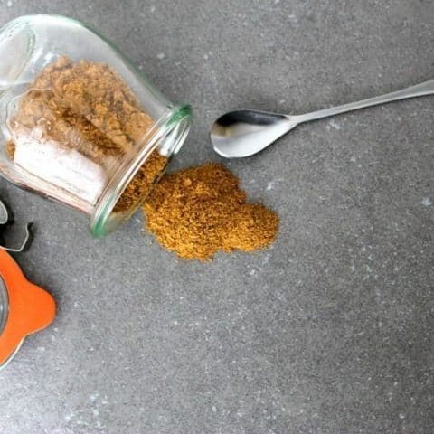 overhead of spicy Chai Spice Mix spilling out of a glass jar on to a table with a spoon next to it.