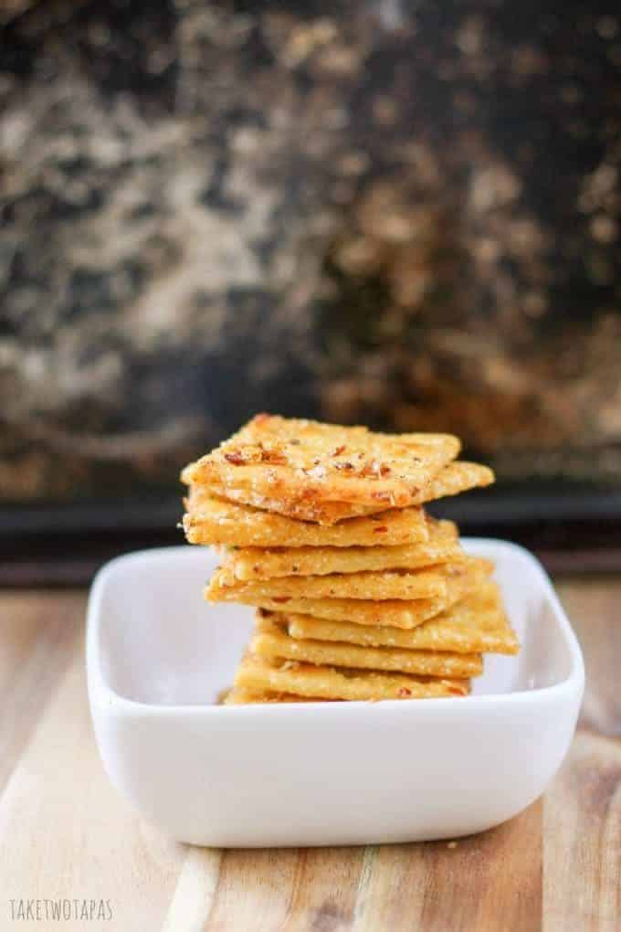 Spicy seasoned saltine crackers in a stack in a white bowl