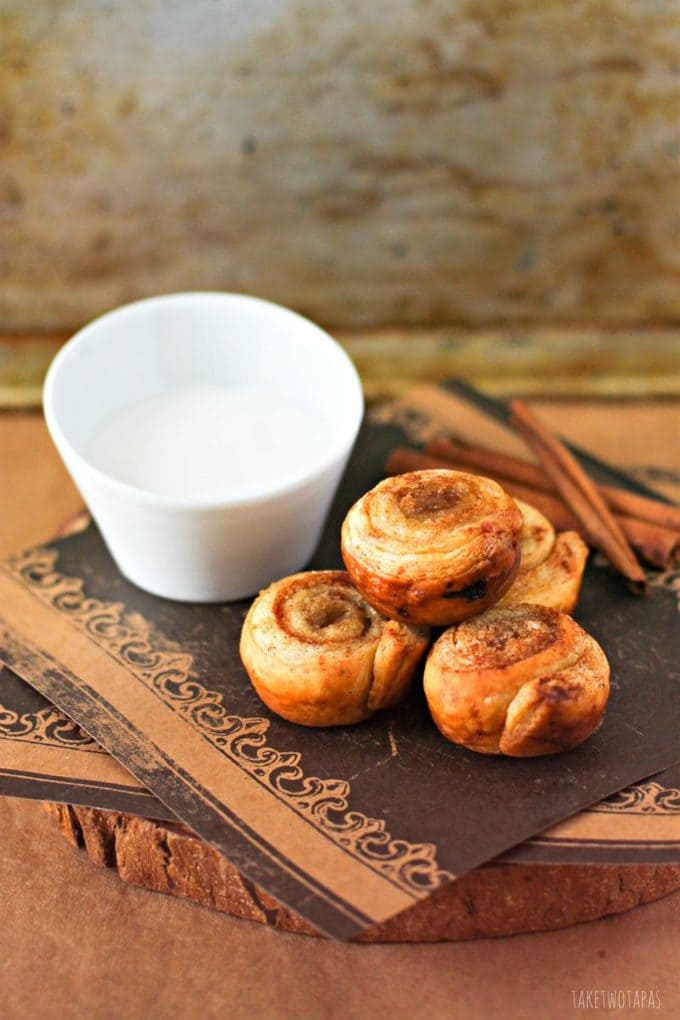 These mini cinnamon roll bites are quickly made with the help of puff pastry. Sprinkled with brown sugar and baked until golden brown, they are crispy on the outside and flaky on the inside. Top them off with vanilla glaze for the perfect bite! Mini Puff Pastry Cinnamon Roll Bites Recipe | Take Two Tapas | #PuffPastry #CinnamonRolls #Breakfast