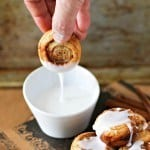 Hand dipping a cinnamon roll in to a small white bowl of icing