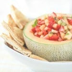 Salsa in a cantalope with chips in a white bowl