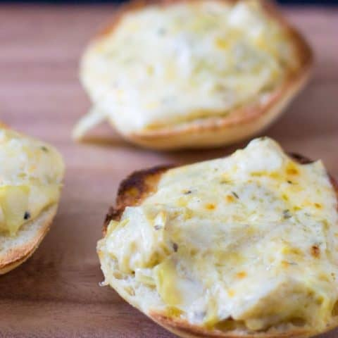 Close up of Warm and gooey cheese toast is made even tastier with roasted garlic and tangy marinated artichokes.
