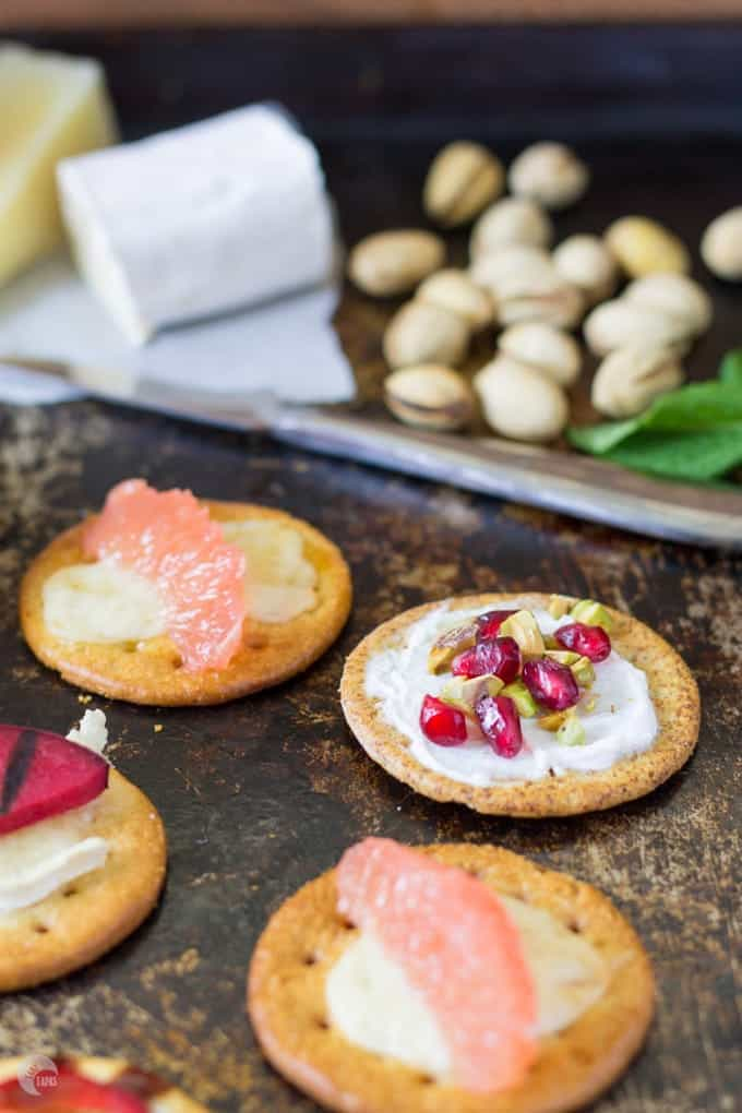 grilled crackers on a sheet pan and goat cheese and pistachios in the background