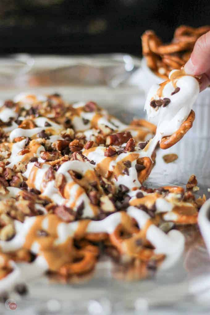 Salty pretzels used as chips and topped with peanut butter, marshmallow cream, chocolate chips, and buttery toasted pecans | Take Two Tapas | #Pretzels #Nachos #Dessert #PeanutButter