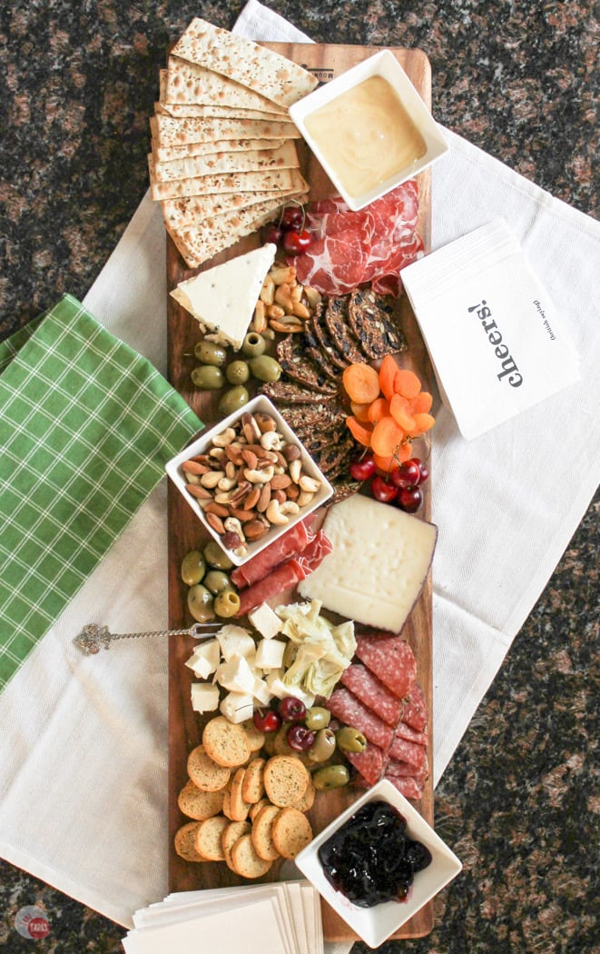 Overhead picture of the antipasto cheese board. Full of fruits, meats, cheeses, nuts, and olives.