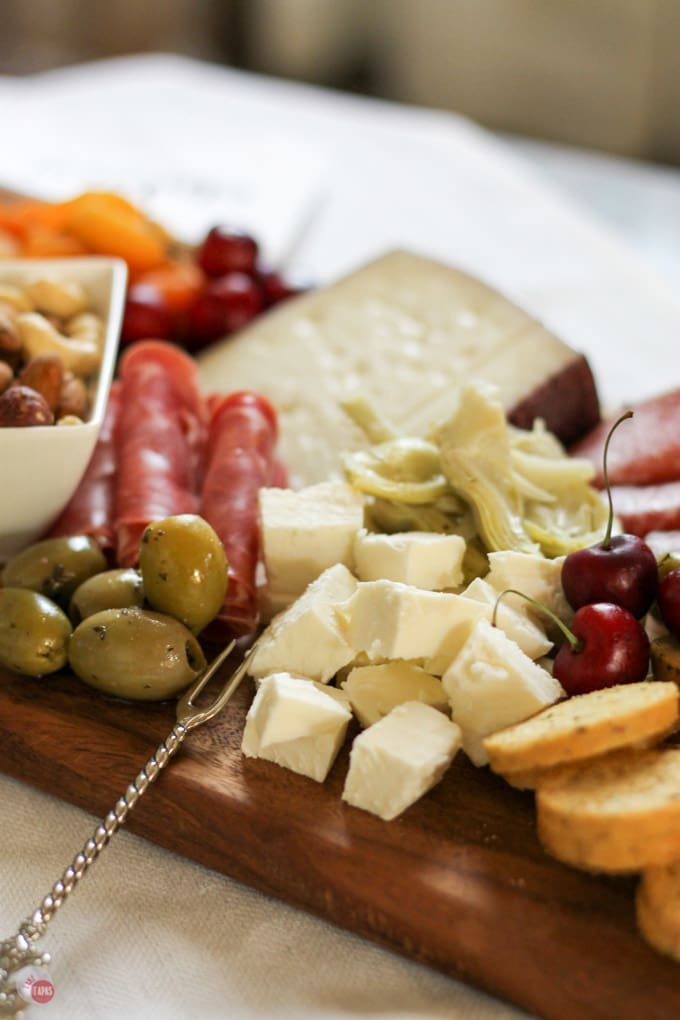 Up close of cheese, olives and meats on the summer tapas cheese board