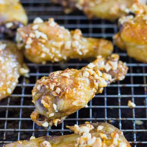 close up of Orange Cashew Chicken Wings on a cooling rack
