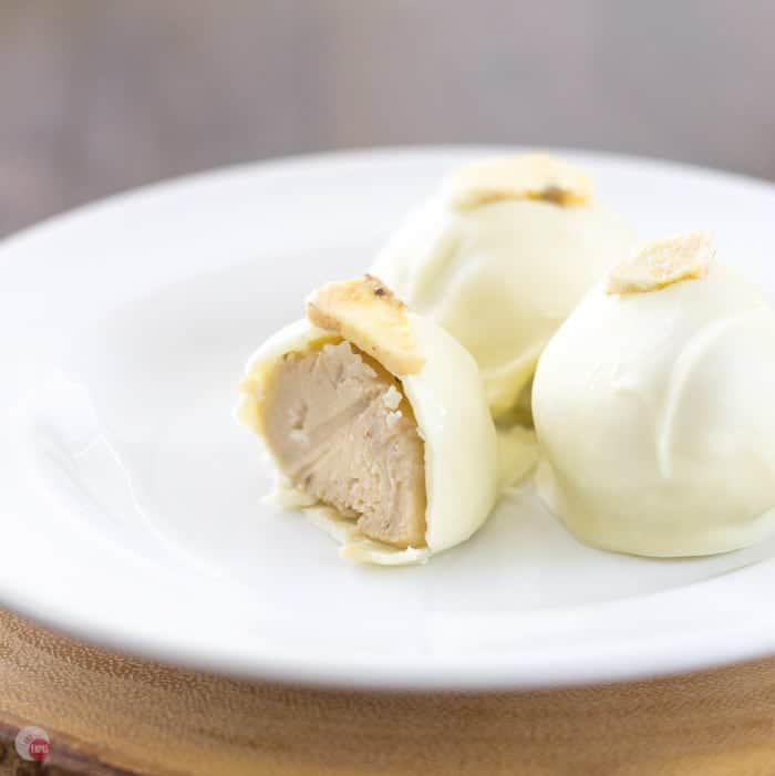 Close up of Creamy Banana Pudding Truffles on a white plate and one has a bite taken out of it.