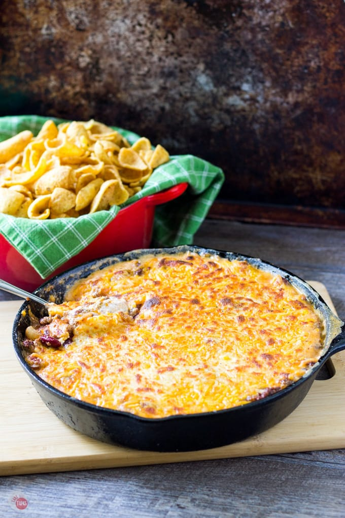 The classic Frito Pie dish containing corn chips, chili, and cheese is transformed into a dip you can scoop into your mouth with reckless abandon! Frito Pie Dip Recipe | Take Two Tapas | #FritoPie #Dips #SkilletDips