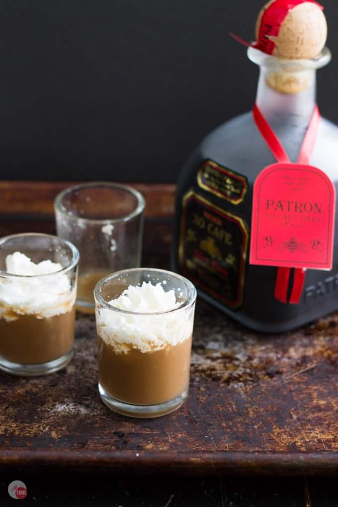 White russian shots and a bottle of Patron on a dark surface