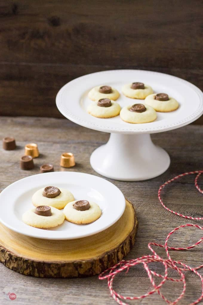 Salted rolo thumbprrint cookies on a white latter and on a white plate both on a wood surface.