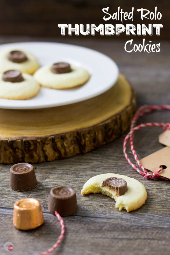"""thumbprint cookies on a white plate, rolos, and a half eaten cookie on a wood surface and text """"salted rolo thumbprint cookies"""""""