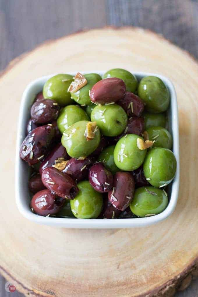 overhead of marinated olives in a white bowl on a wood serving platter