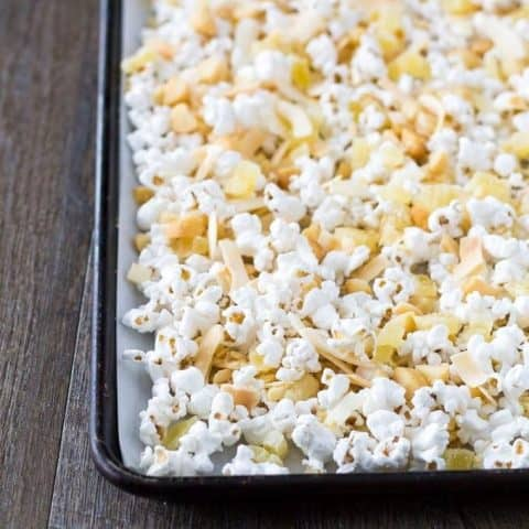Popcorn mixture spread out on a sheet pan.