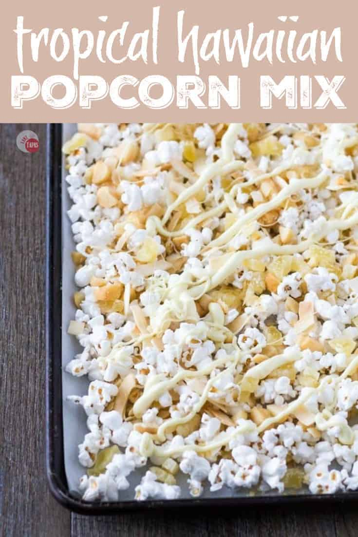 A tropical snack mix of dried pineapple, toasted coconut chips, roasted macadamia nuts, drizzled with white chocolate.  Perfect for a slightly healthy popcorn snack mix for those days when you are craving everything! Tropical Hawaiian Popcorn Mix Recipe | Take Two Tapas | #Popcorn #Hawaiian #PopcornSnack #HealthySnacks #TrailMix #HealthyPopcornRecipe