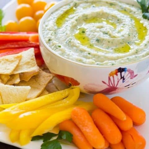 White Bean Parsley Hummus in a white bowl and assorted vegetables on a white platter