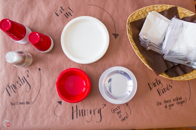 clear and red plastic cups, white plastic plates,red and clear plastic bowls and napkins in a basket all on a brown paper surface