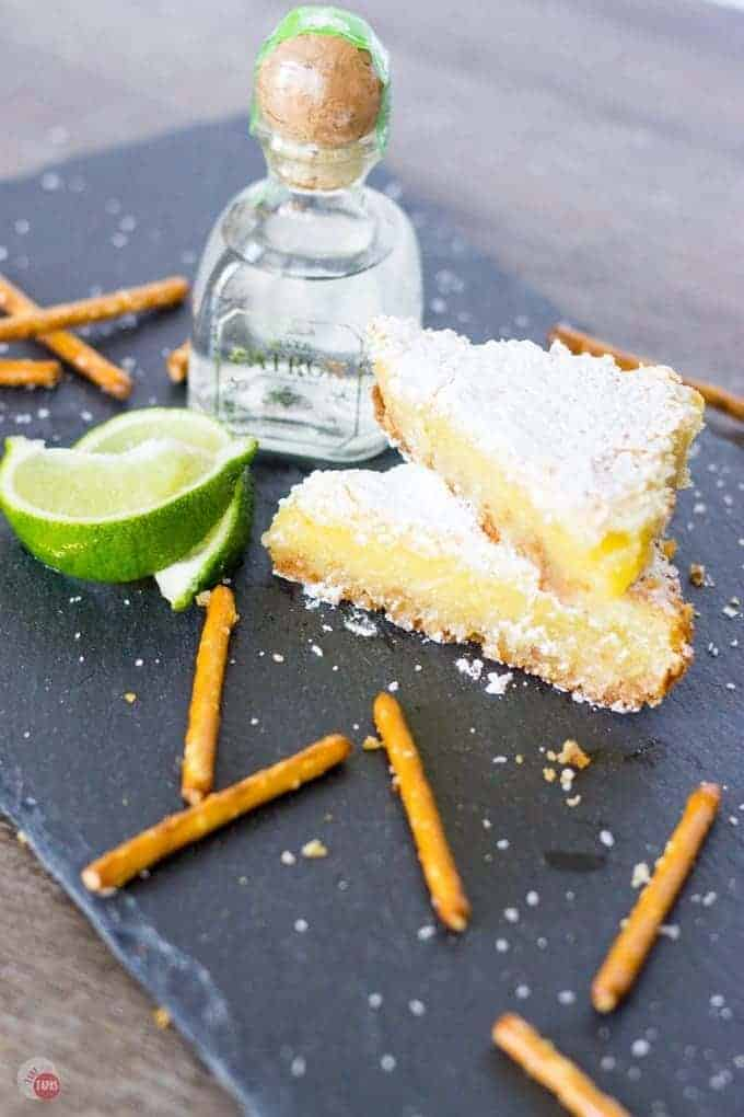 Margarita Bars stacked, pretzel sticks, lime wedges, a small bottle of tequila on a slate board