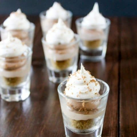 These no-bake cheesecake shooters have Nutella and salted caramel! Topped with whipped cream and chocolate shavings, these mini sweets can be made ahead of time! Nutella Salted Caramel Cheesecake Shooters Recipe | Take Two Tapas | #nutella #SaltedCaramel #PieRecipe #DessertShooters #TinyDesserts #SmallDessertRecipe