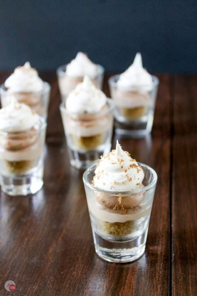 These no-bake cheesecake shooters have Nutella and salted caramel! Topped with whipped cream and chocolate shavings, these mini sweets can be made ahead of time! Nutella Salted Caramel Cheesecake Shooters Recipe   Take Two Tapas   #nutella #SaltedCaramel #PieRecipe #DessertShooters #TinyDesserts #SmallDessertRecipe