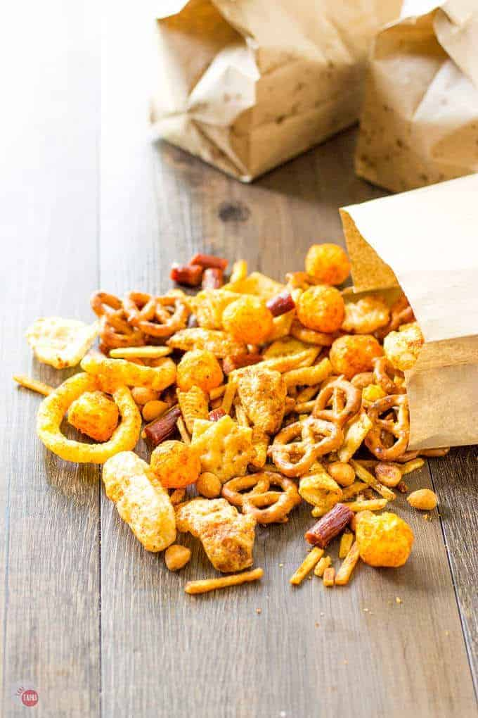 Redneck Snack Mix on a wood surface with brown paper bags in the background