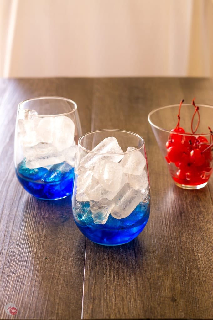 Build your Space Pop Cocktail with blue curacao first. | Take Two Tapas | #PatrioticRecipes #4thofJuly #RedWhiteBlue #CocktailRecipes #VodkaRecipe #SummerHolidays #SummerRecipes