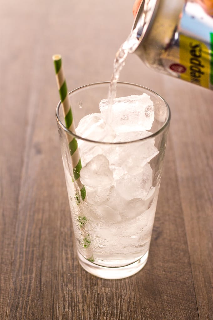Pouring the schweppes in to a glass of ice