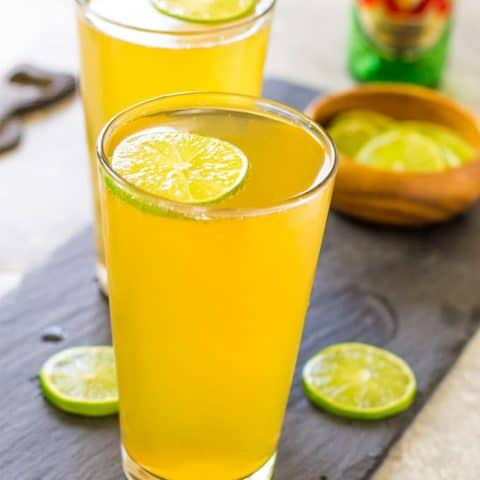 Two 3 Ingredient Margarita Beer Shandy Cocktails on a wood plank.