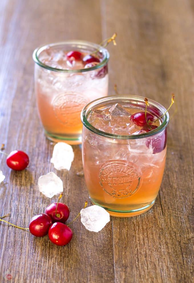 Side angle of two glasses of refreshing Cherry Lime Bourbon Smash