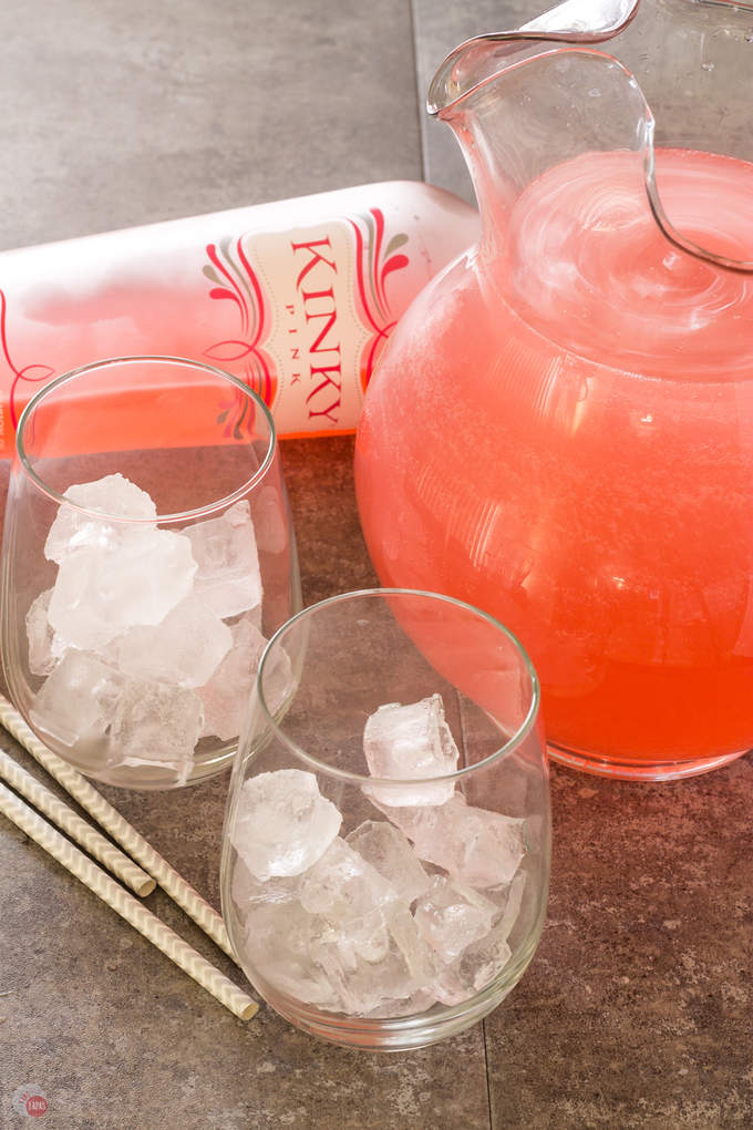 2 glasses with ice, straws, a bottle of pink liquor and a glass pitcher ful of Pink passion party punch on a gray surface