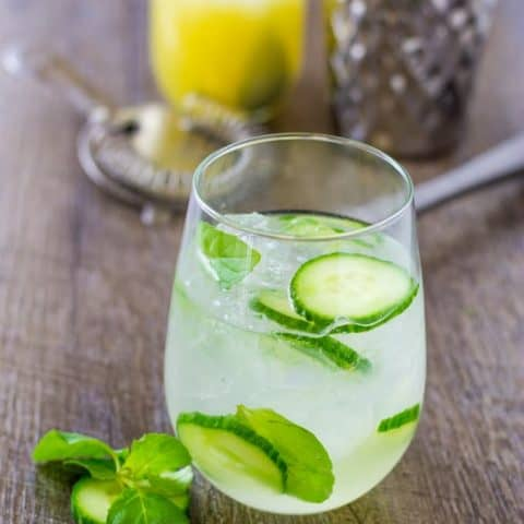 Herbaceous Cucumber Mint Gin Cooler with lime sparkling water on a wood table with tools to make it in the background.