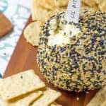 Wasabi Ginger Cheese Ball sitting on a cutting board surrounded by crackers
