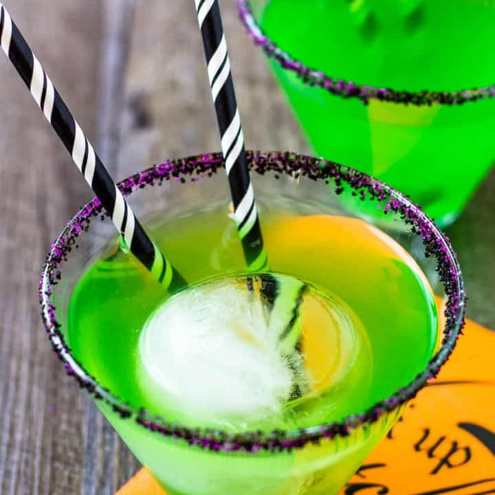close up of green flying monkey halloween cocktail with 2 black striped straws in it