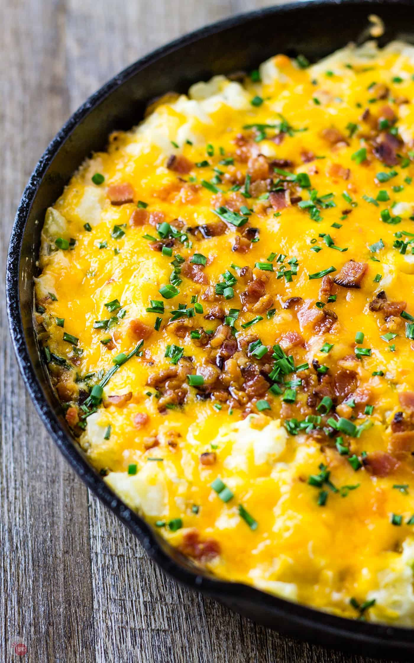Loaded Potato Skin Dip all together in a skillet sitting on a wood table
