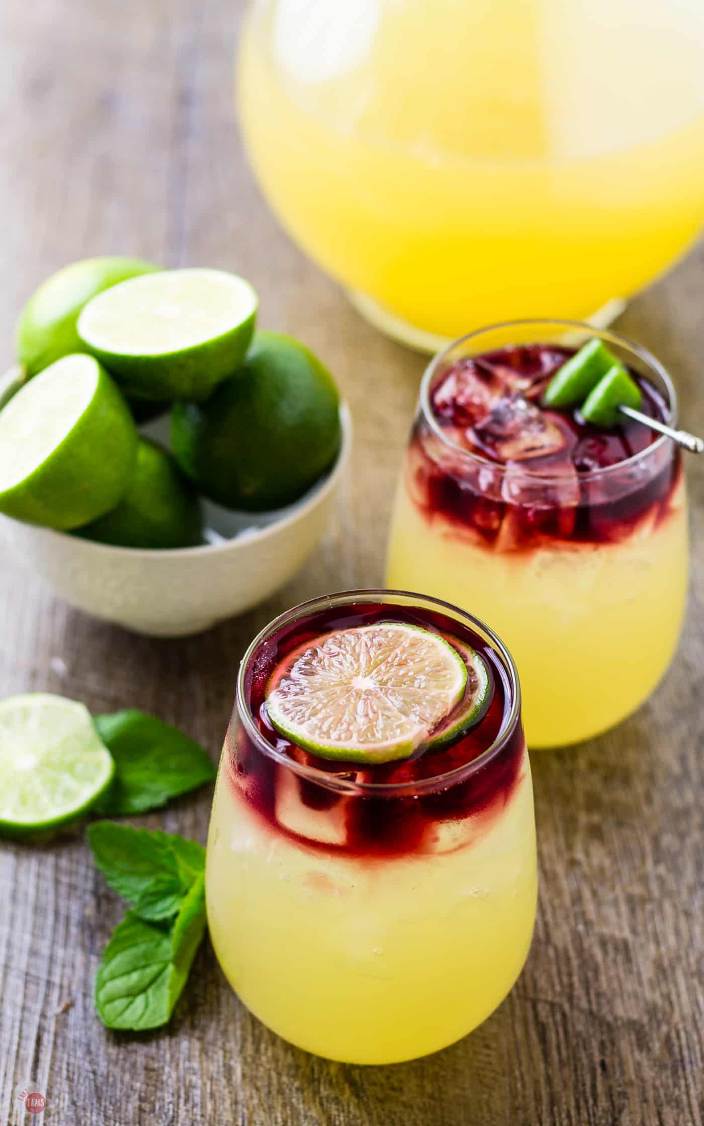 The layered look of the Wimade comes from the dark red wine or juice poured slowly on top of the limeade | Take Two Tapas | #Wimade #Wine #Limeade #HoneyLimeade #Wine #LayeredCocktail