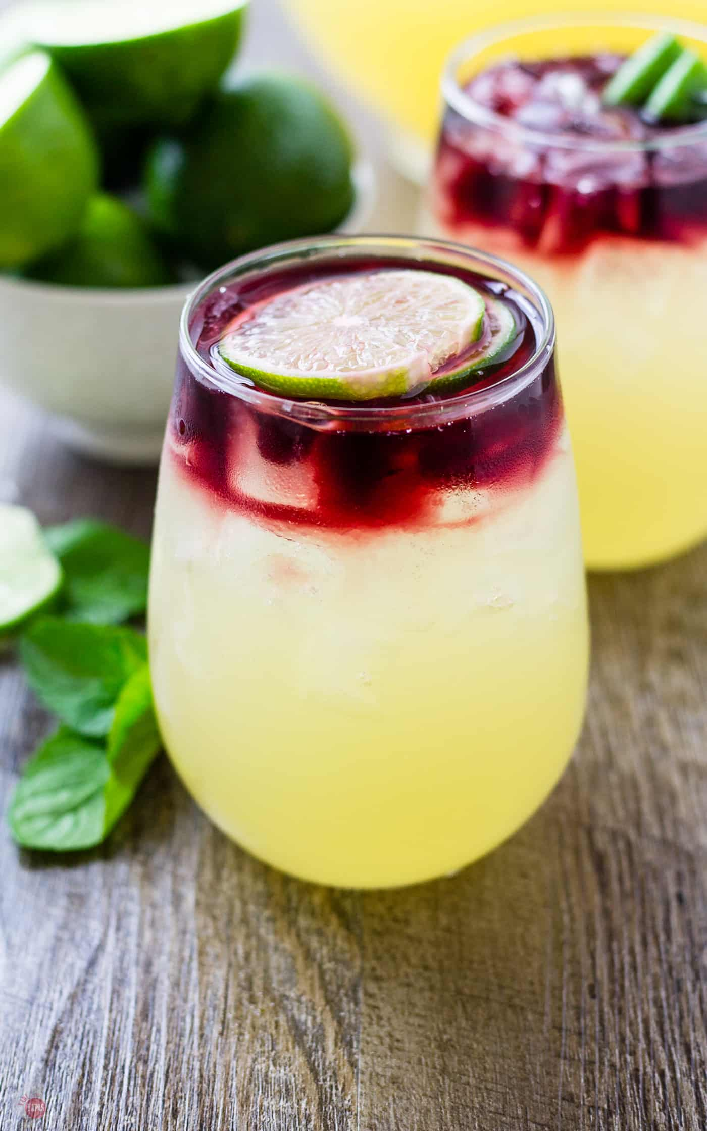 Get the stunning layered look of the Wimade by pouring your wine onto a slice of lime so it diffuses gently over the homemade honey limeade | Take Two Tapas | #Wimade #Wine #Limeade #HoneyLimeade #Wine #LayeredCocktail