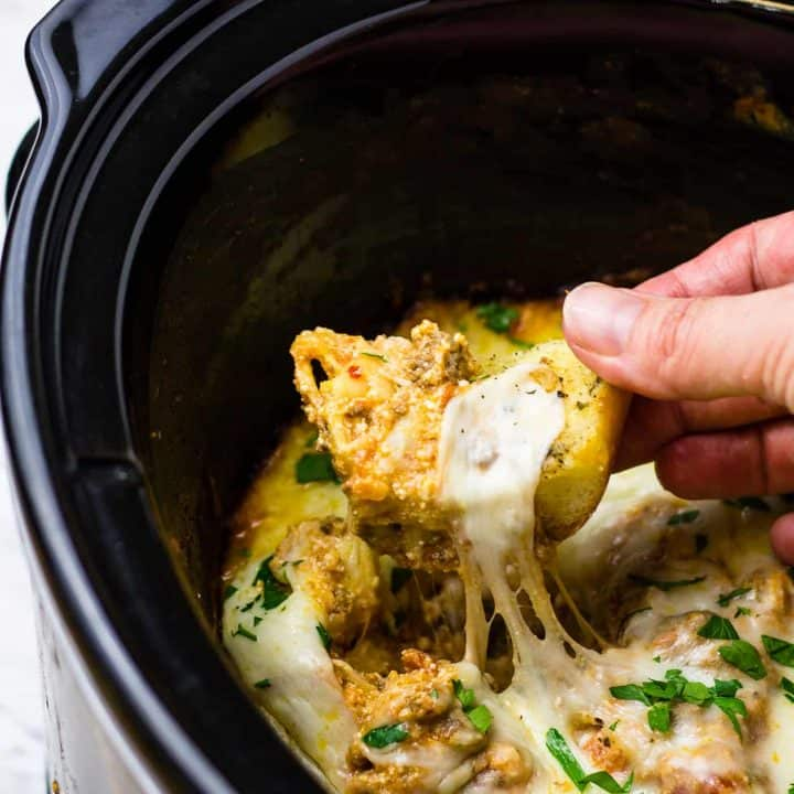 Hand dipping breadstick into the extra cheesy lasagna dip, in a crockpot!