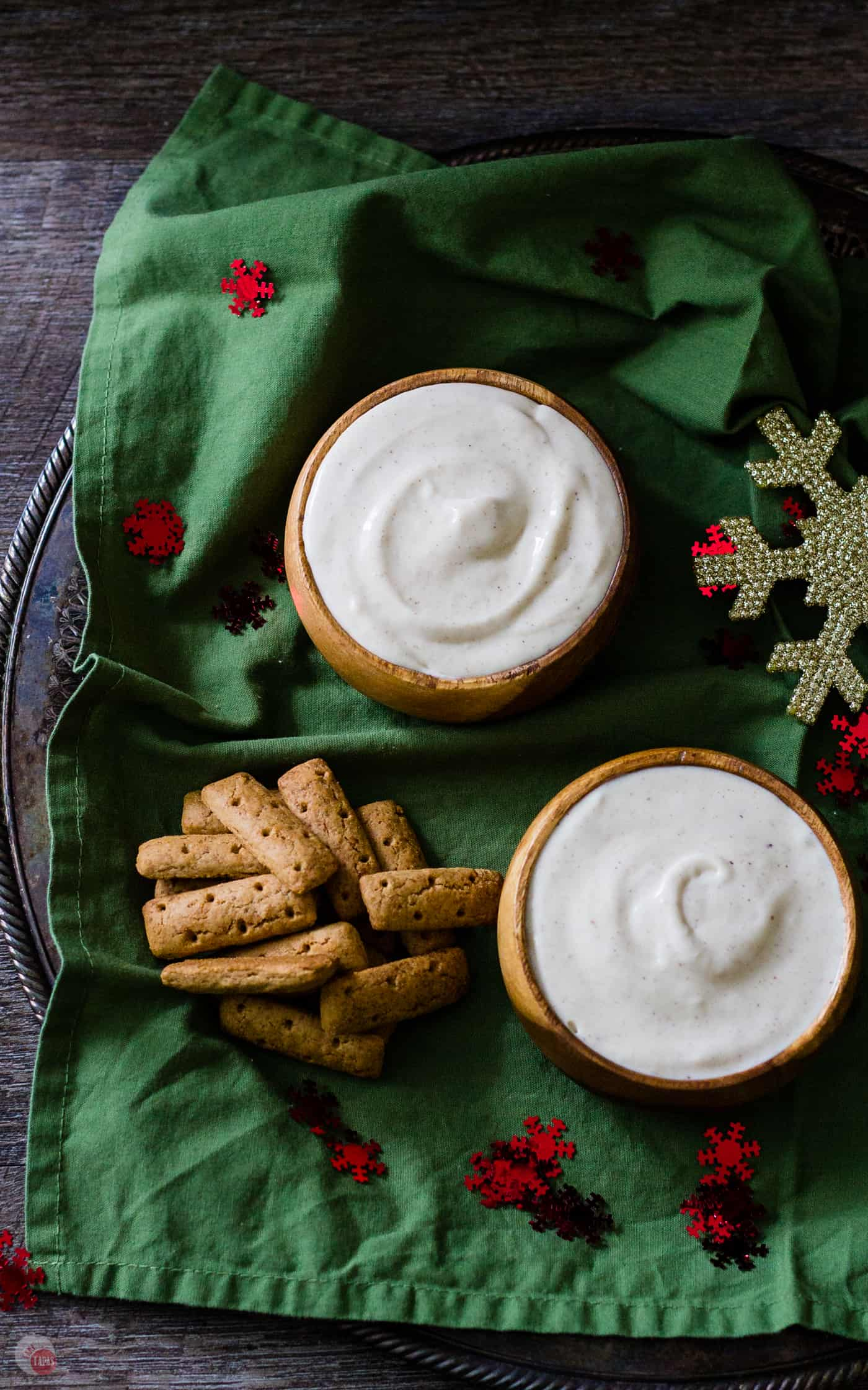 overhead picture of two bowls of eggnog dip on green napkin