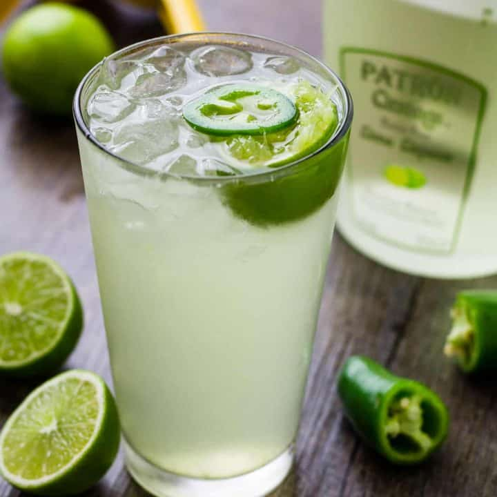 Lime Coconut Cooler Cocktail with sparkling water on a table surrounded by liquor bottle, jalapenos and cut limes.